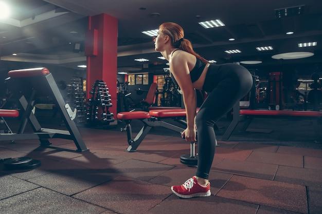 機器の健康健康的なライフスタイルとジムで練習している若い筋肉の白人女性