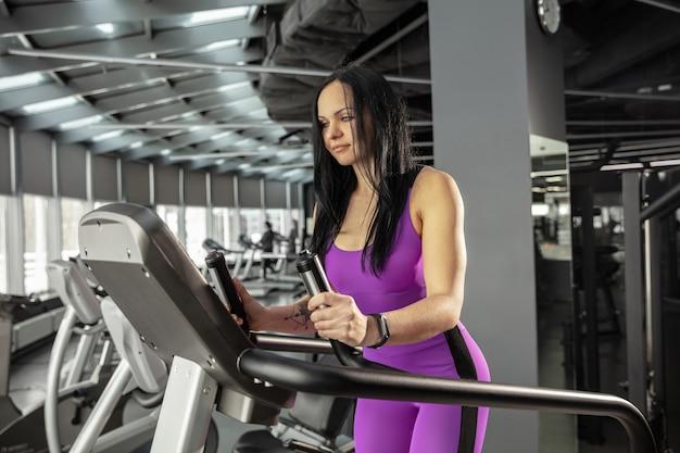 機器を備えたジムで練習している若い筋肉の白人女性