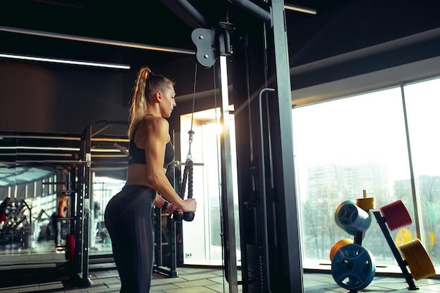 ウェイトを使ってジムで練習している若い筋肉の白人女性。筋力トレーニングを行い、下半身、脚をトレーニングするアスリート女性モデル。