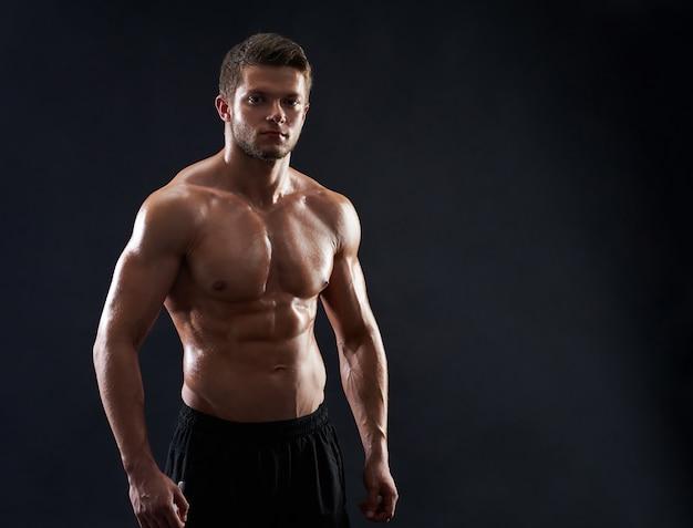 Молодой мускулистый спортсмен позирует без рубашки на черном фоне