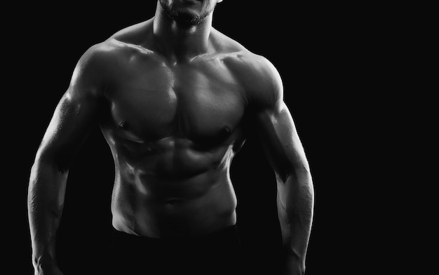 검은 backgroun에 shirtless 포즈를 취하는 젊은 근육질의 스포츠맨