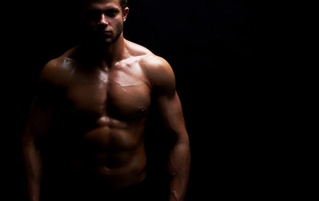 셔츠를 입지 않은 채 포즈를 취하는 젊은 근육질의 스포츠맨