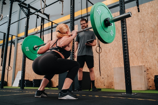 Молодая мускулистая девушка поднимает штангу мертвого веса в тренажерном зале crossfit
