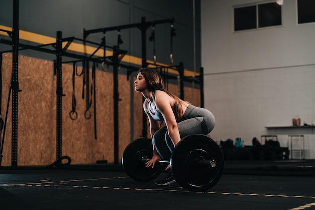 クロスフィット体育館で自重バーベルを持ち上げる若い筋肉の女の子