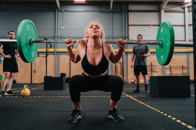 Young muscular girl lifting a dead weight barbell in a crossfit gymnasium