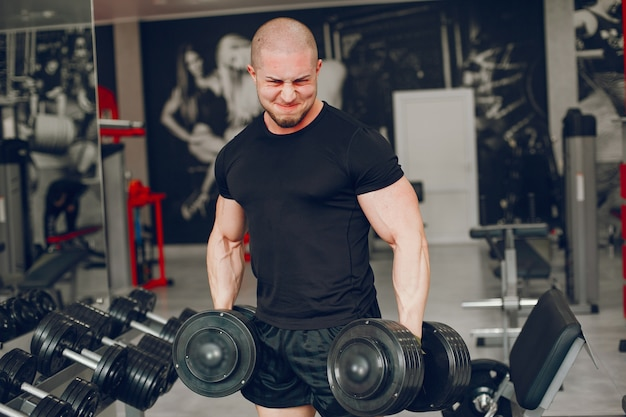 A young and muscular guy in a black t-shirt trains in a gym