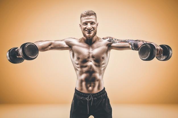 Молодой мускулистый парень качает дельты с гантелями на оранжевом фоне. концепция фитнеса и питания. смешанная техника