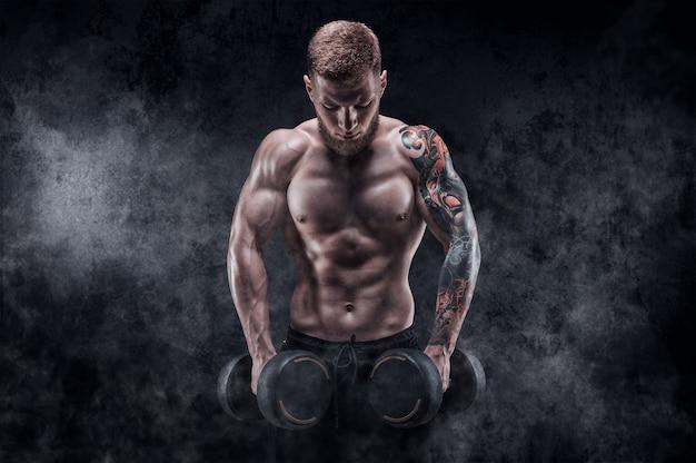 Молодой мускулистый парень качает трапециевидные мышцы. концепция фитнеса и питания. смешанная техника