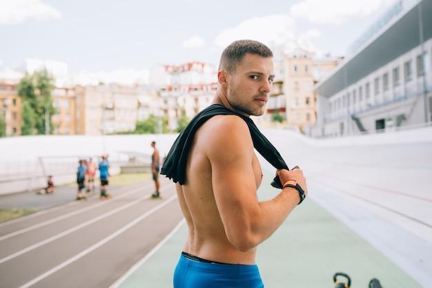 그의 어깨 너머로 다시 찾고 젊은 근육 질의 남자. 잘 생긴 남자 파란색 반바지의 초상화.