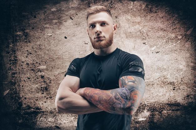 Молодой мускулистый парень позирует на фоне бетонной стены. концепция фитнеса и питания. смешанная техника