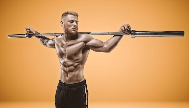 Молодой мускулистый парень позирует со штангой на плечах на оранжевом фоне. концепция фитнеса и питания. смешанная техника
