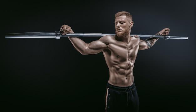 Молодой мускулистый парень позирует со штангой на плечах на черном фоне. концепция фитнеса и питания. смешанная техника