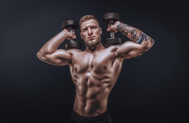 Молодой мускулистый парень позирует с гантелями в студии. прокачка плеча. концепция фитнеса и бодибилдинга. смешанная техника