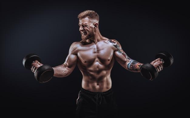 Молодой мускулистый парень качает бицепс с гантелями. концентрированное сгибание. концепция фитнеса и питания. смешанная техника