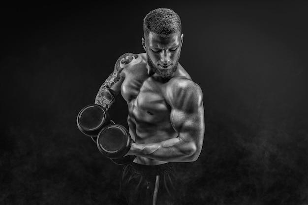 Молодой мускулистый парень качает бицепс с гантелями. концепция фитнеса и питания. смешанная техника