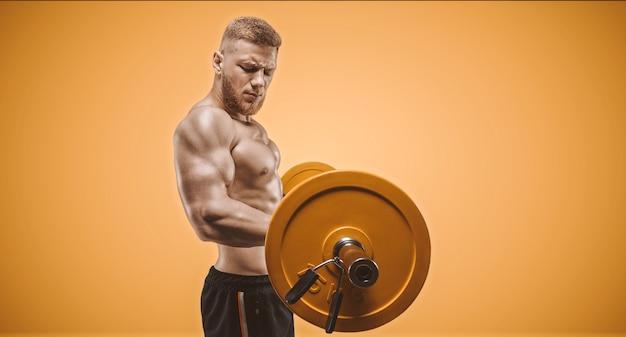 Молодой мускулистый парень качает бицепсы со штангой на оранжевом фоне. концепция фитнеса и питания. смешанная техника
