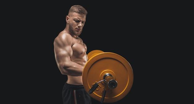 Молодой мускулистый парень качает бицепс штангой на черном фоне. концепция фитнеса и питания. смешанная техника