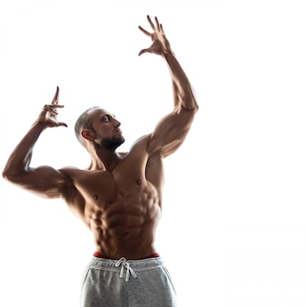 Young muscular guy on white background