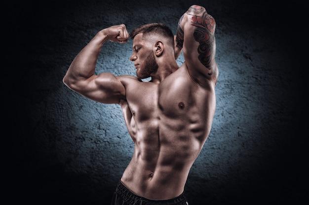 Молодой мускулистый парень с красивым прессом позирует на фоне синего пятна. концепция фитнеса и питания. смешанная техника
