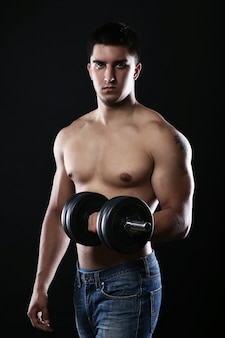 Young and muscular guy with dumbbell