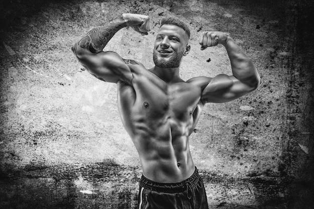 Молодой мускулистый парень с красивым прессом позирует на фоне бетонной стены. концепция фитнеса и питания. смешанная техника