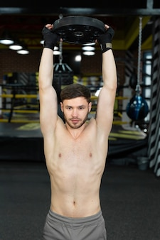 Young muscular guy with a naked torso posing holding a pancake from a barbell