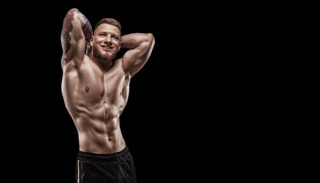 Молодой мускулистый парень с красивым прессом позирует на черном фоне. концепция фитнеса и питания. смешанная техника