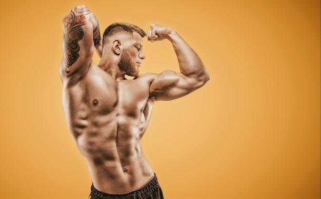 Молодой мускулистый парень с красивым прессом позирует на оранжевом фоне. концепция фитнеса и питания. смешанная техника