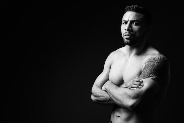 Молодой мускулистый латиноамериканец без рубашки на черном