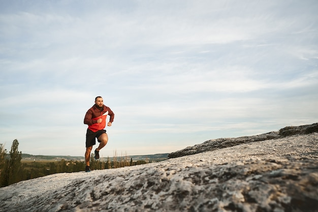 Young muscular male athlete running up the hill