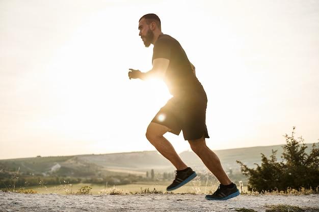 Молодой мускулистый спортсмен-мужчина, бегущий в гору