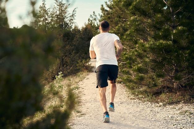 丘を駆け上がる若い筋肉質の男性アスリート