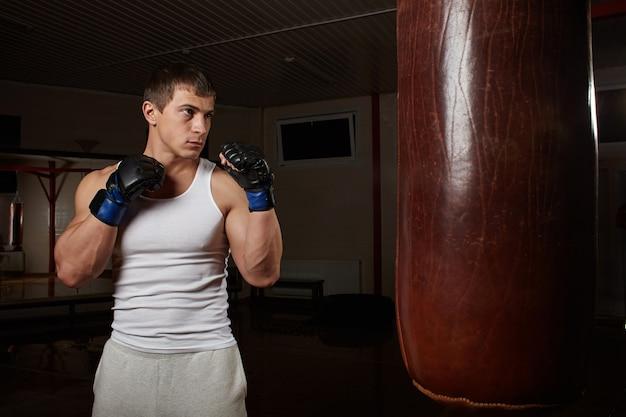 Молодой мускулистый боксер тренируется с боксерской грушей в темном интерьере