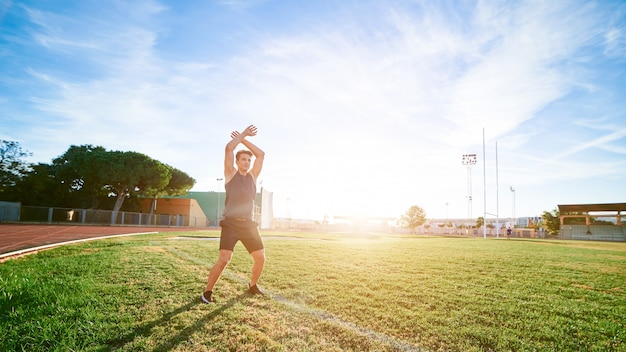 Young muscular man doing exercises on stadium