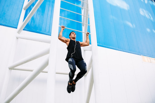 Young muscular man doing pull ups, listening to music in headphones during workout