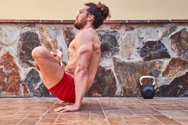 Молодой мышечный человек делая тренировку йоги дома. концепция домашнего обучения и здорового образа жизни.