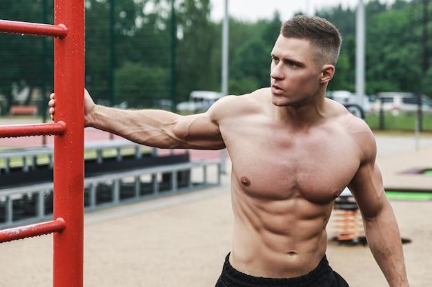 Молодой мускулистый мужчина во время тренировки на улице