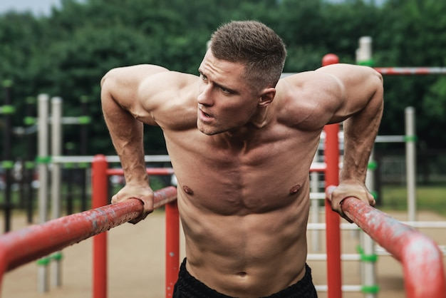 Young muscular man during his workout on the street