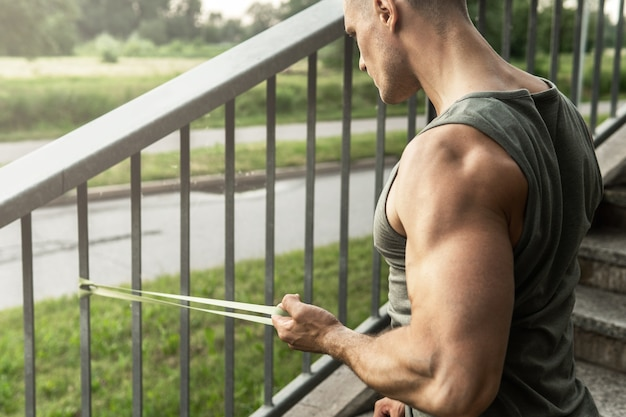 Young and muscular man during workout with a resistance rubber band on a street.