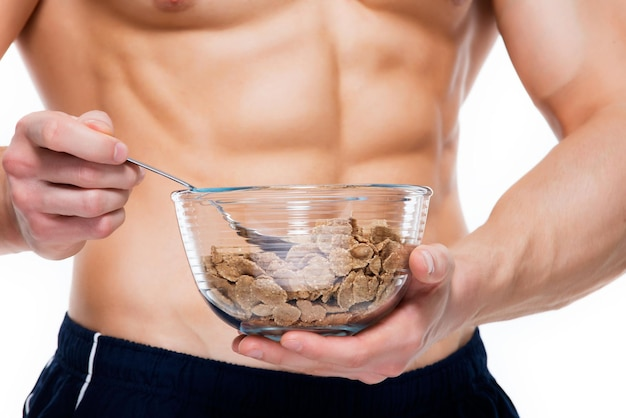 Young muscular man holds a plate with flakes