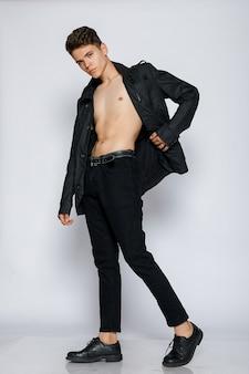 黒のジャケットとジーンズの若い筋肉質の男。若いハンサムな男、裸の胴体に革をジャック、感情的なポーズ、白い背景、現代人、ライフスタイルの人々の概念