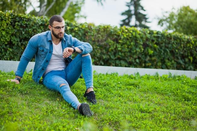 カジュアルな服装の若い筋肉質の男は、腕時計を見て草の上に座っています。筋肉質な人、デートを待っているマッチョな男
