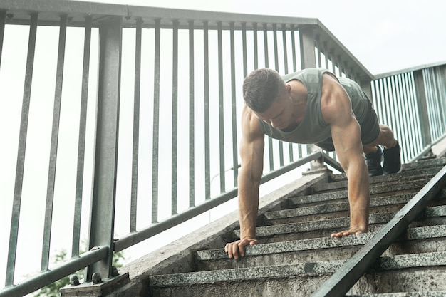 Young and muscular man is doing push-ups during calisthenic workout on a street