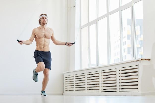 스포츠 훈련 중 밧줄을 건너 뛰는 젊은 근육 남자