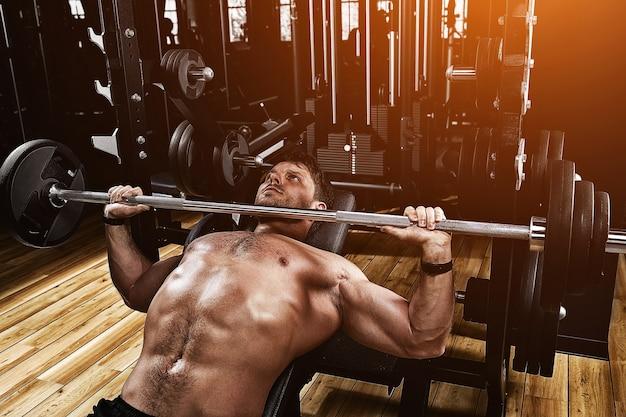 체육관에서 바벨 벤치 프레스를 들어 올려 젊은 근육 질의 남자. 아름다운 몸매, 목표 달성, 삶의 방식으로서의 스포츠.