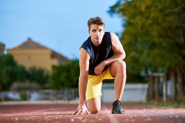 Young muscular man posing on a stadium track