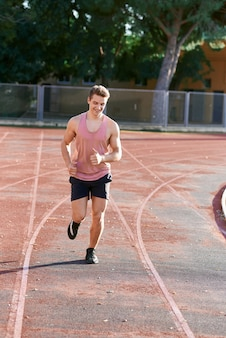Young muscular man running on the track