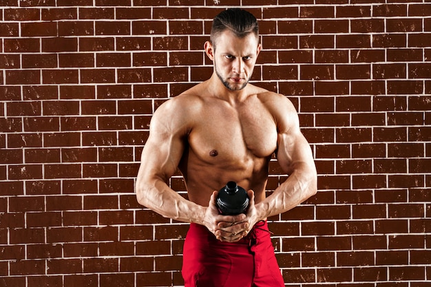 Young muscular man showing his perfect body and shaker