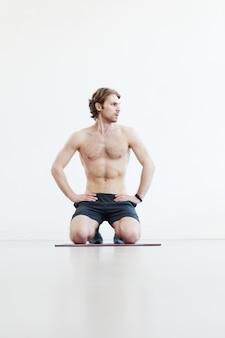 床に座って、白い背景に対してトレーニング後に休んでいる若い筋肉の男