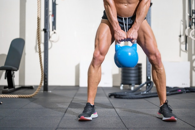 Young muscular man training with kettlebells